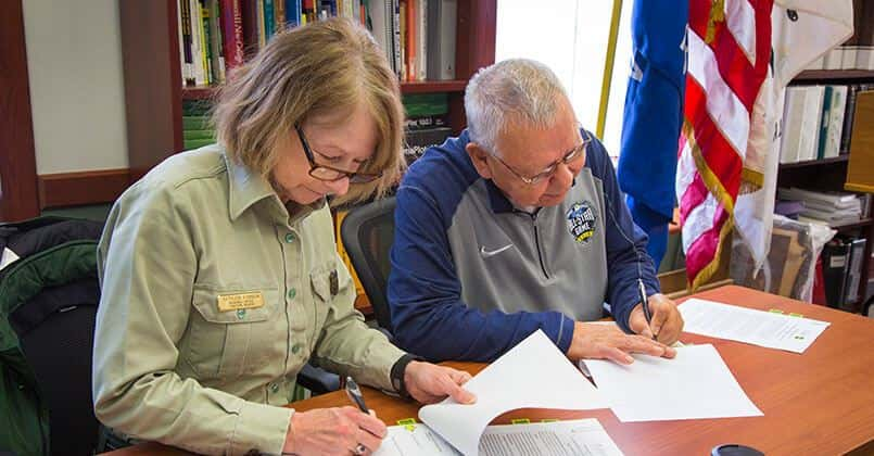 """U.S. Forest Service Eastern Regional Forester Kathleen Atkinson and FCP Chairman Harold """"Gus"""" Frank sign the MOU."""